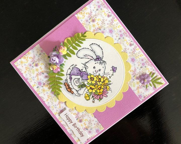 Hand made birthday card with a stamped rabbit image and spring flowers