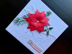 Hand made Christmas card with die cut poinsettia and snowflake on white embossed background