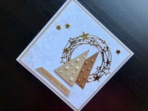 Hand made Christmas card with triangular Christmas trees and a gold star wreath