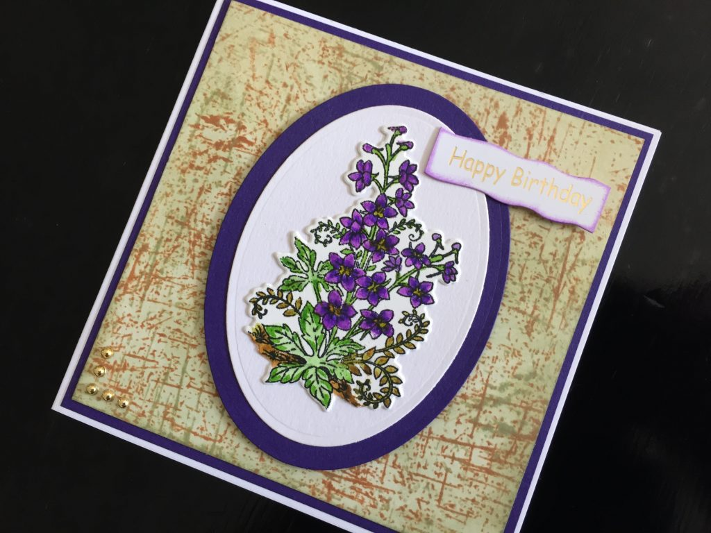 Hand made birthday card with stamped and die cut larkspur, on a stamped and inked background.
