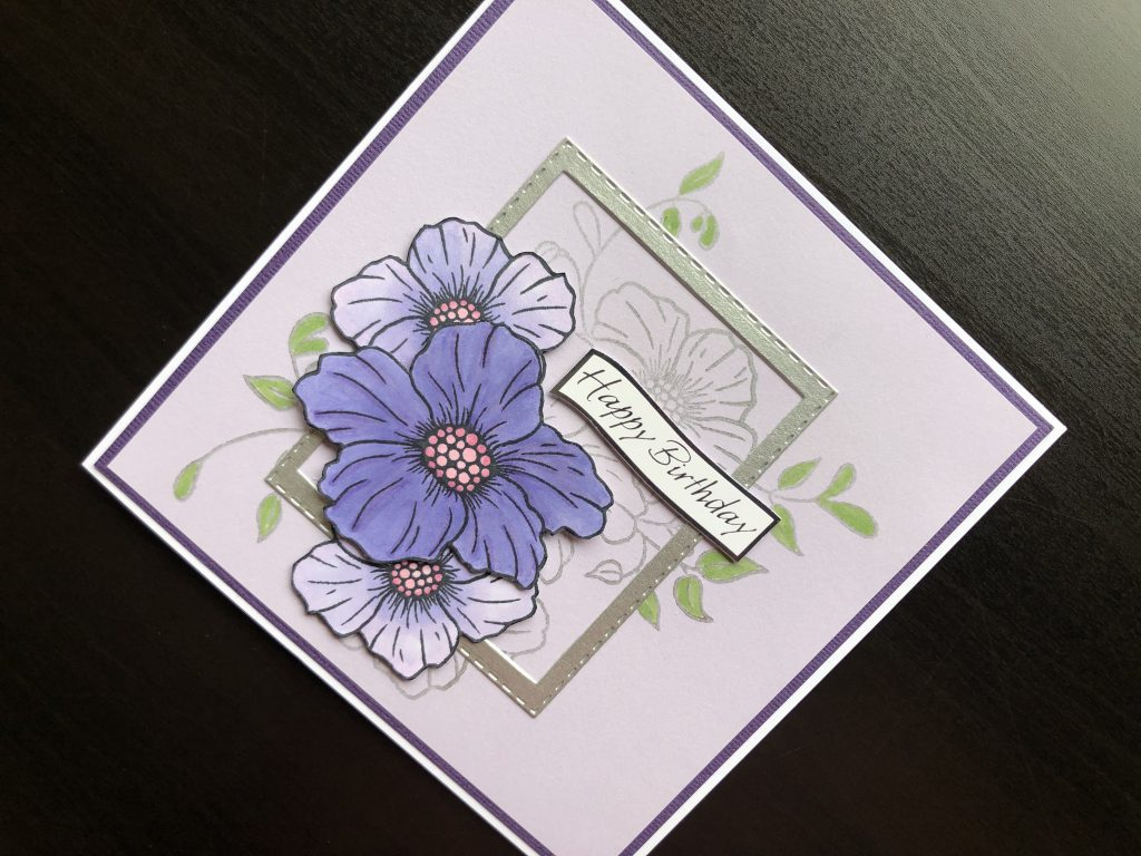 Hand made birthday card with stamped flowers and die cut frame.