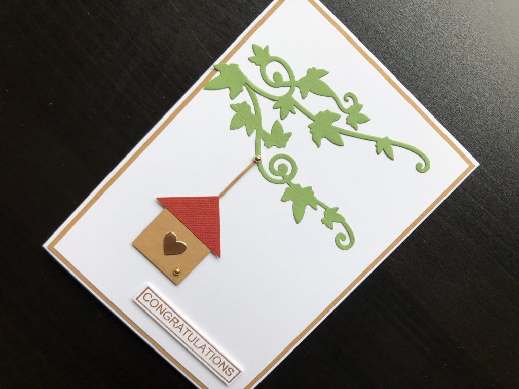 Hand made new home card with die cut branches and bird house and stamped congratulations greeting.