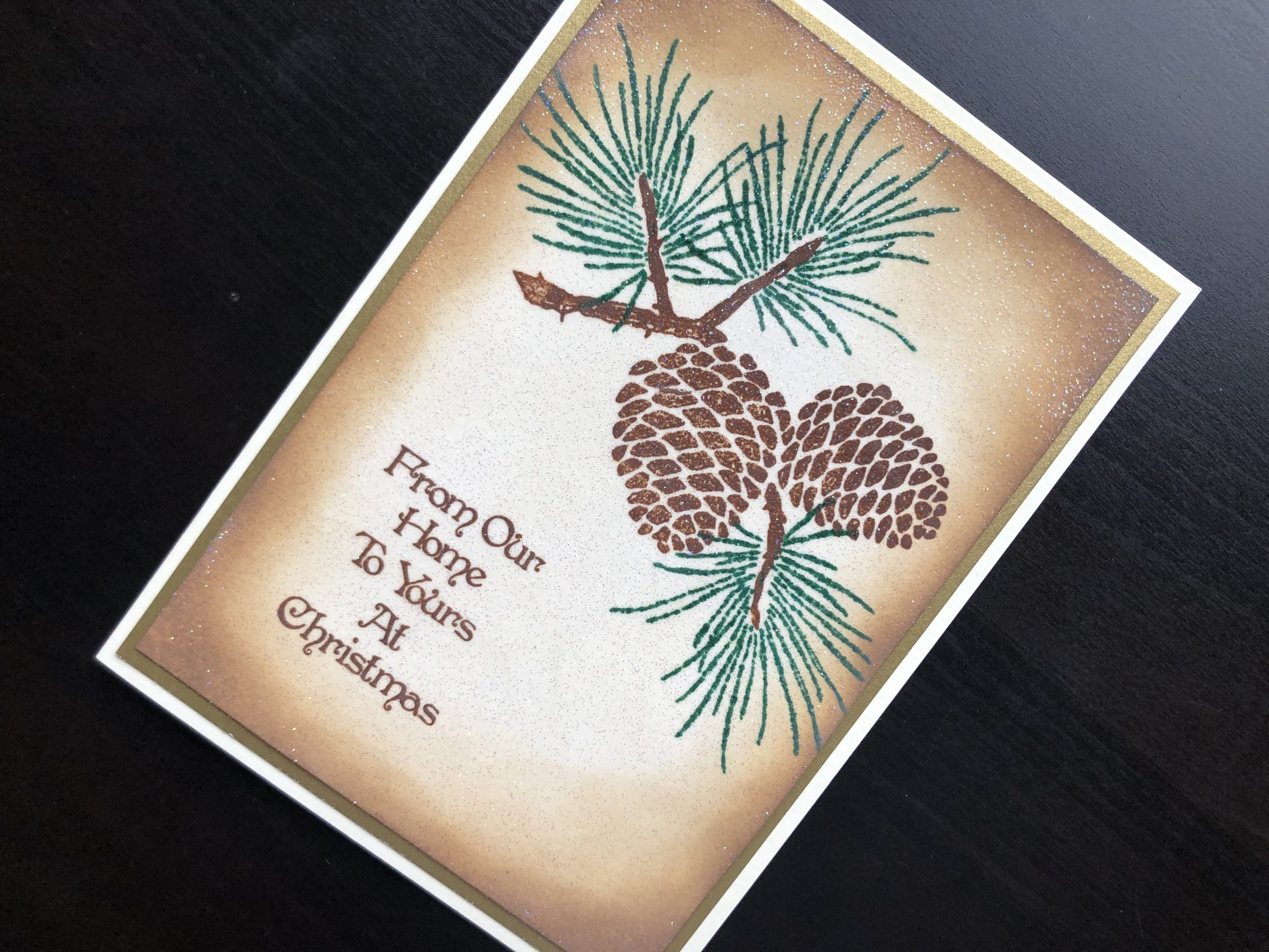 hand made Christmas card with stamped pine cones and glitter embossing