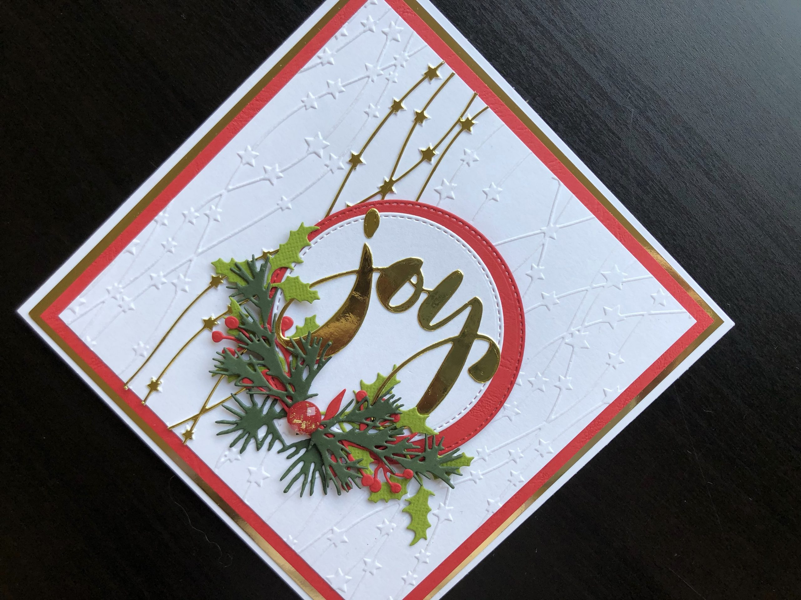 Hand made Christmas card with die cut sentiment and foliage and embossed background