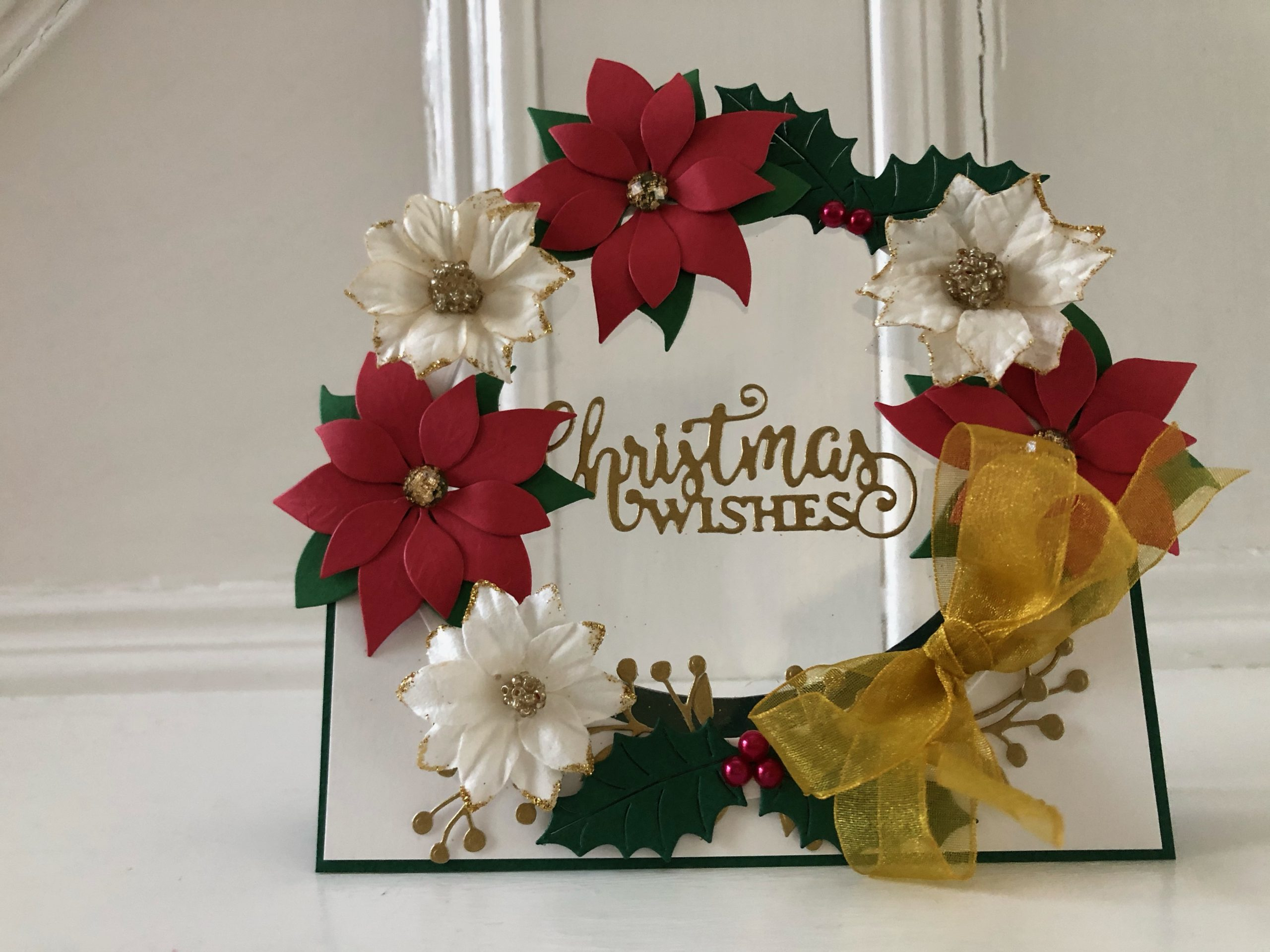 hand made christmas card with flower and holly wreath