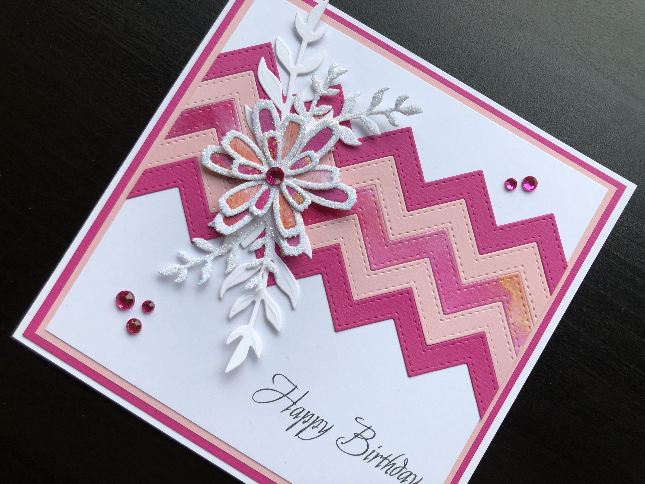 Hand made birthday card with die cut zigzag panel, flowers and leafy stems