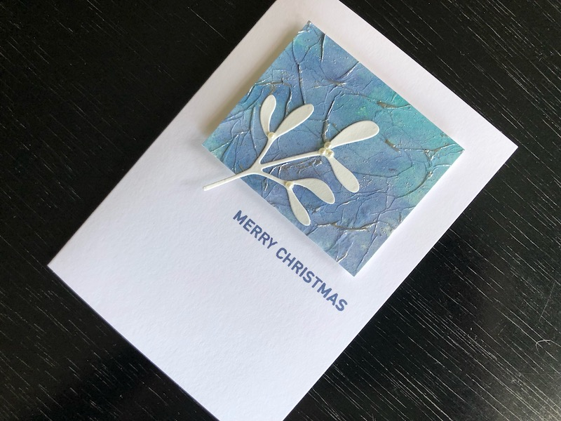 Hand made Christmas card with inked and heat embossed tissue panel and die cut mistletoe