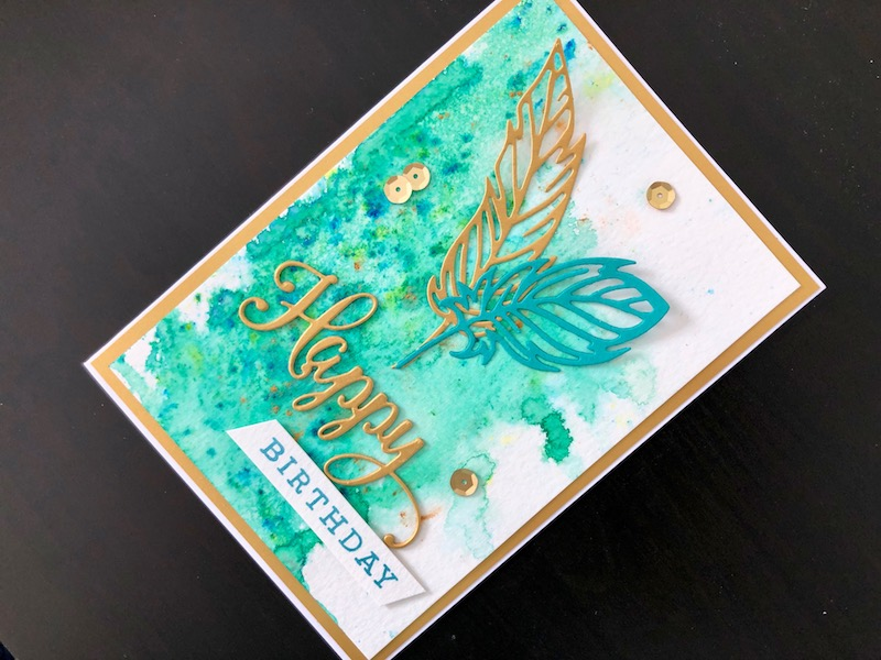 Happy birthday card with die cut feathers and pixie powder background