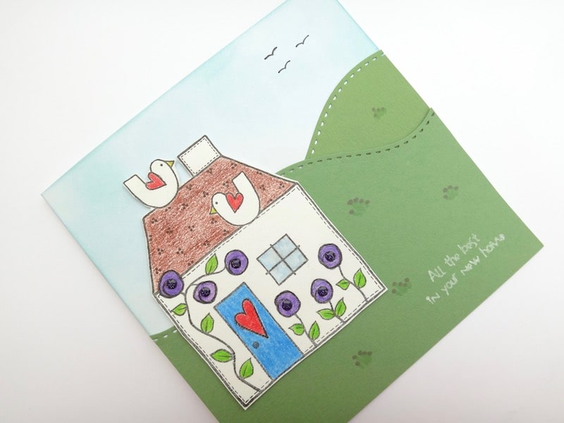 New home card with die cut stitched hillsides and stamped house.