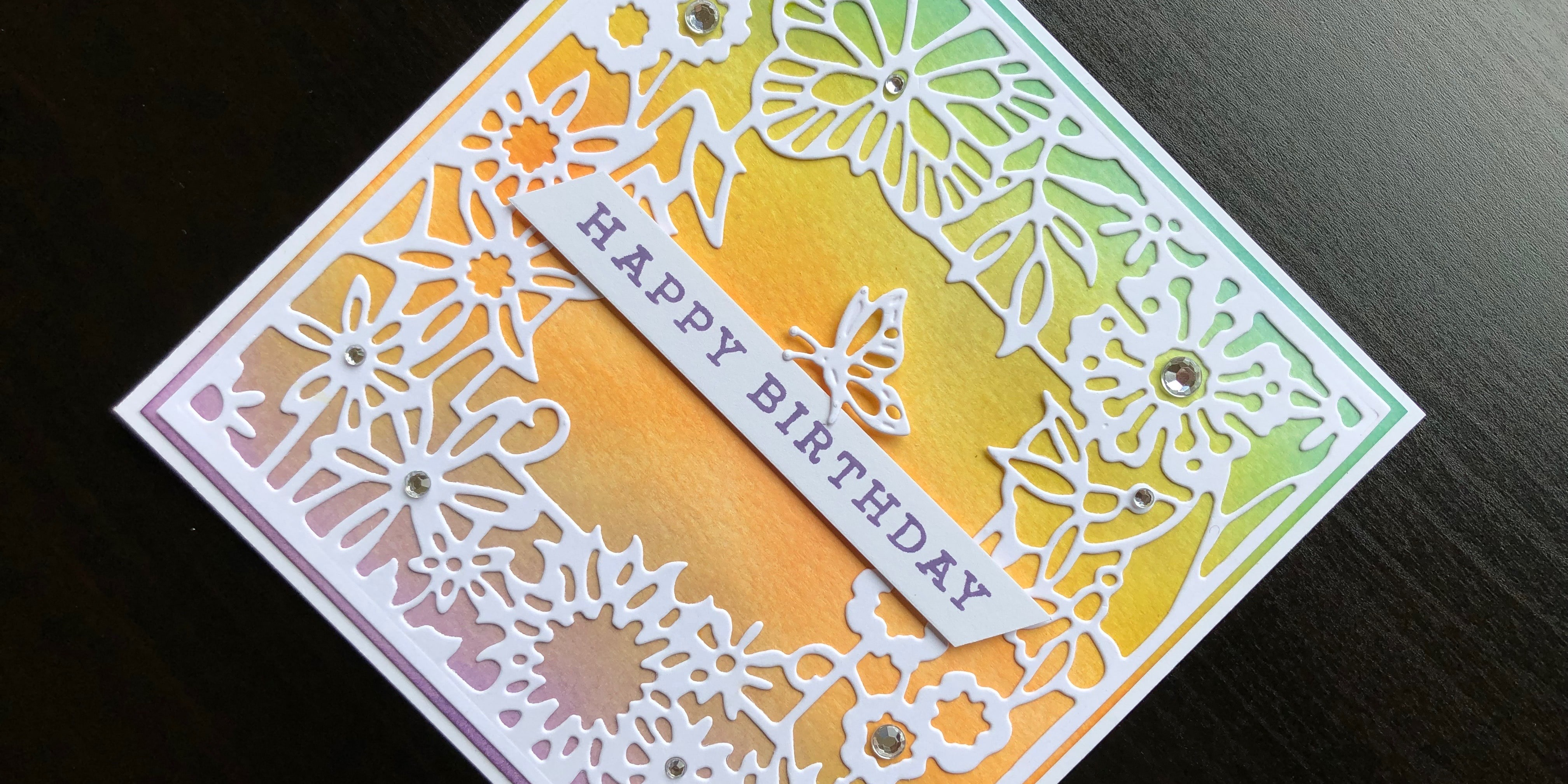 hand made birthday card with an inked background and die cut butterfly frame